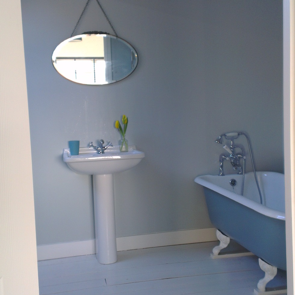 Dove grey bathroom with teal bath and vintage mirror