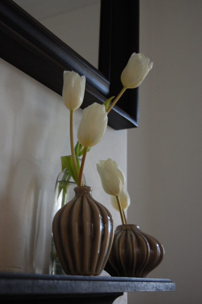 Monochrome mantelpieces - white tulips in small vases