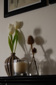 Small mantelpiece display with flowers, vases and candle