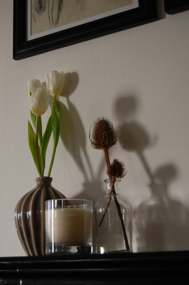 Small monochrome mantelpiece display with flowers, vases and candle