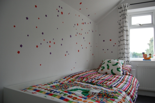 2-year-old boy's bedroom with star wall stickers and hungry caterpillar quilt